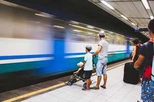 A family waits on a subway platform in Naples, Italy