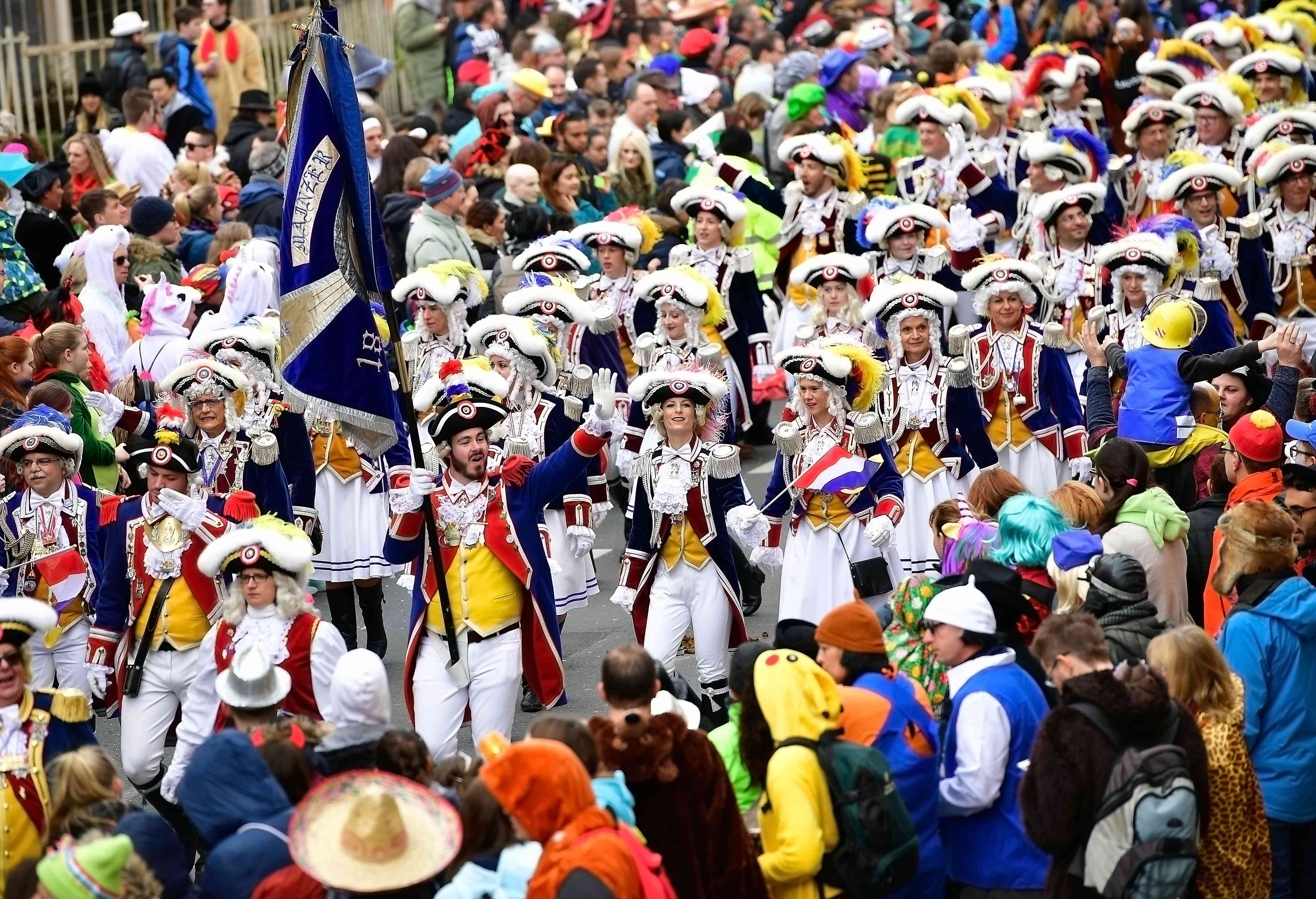 People marching in parade in Mainz Germany wearing historical costumes