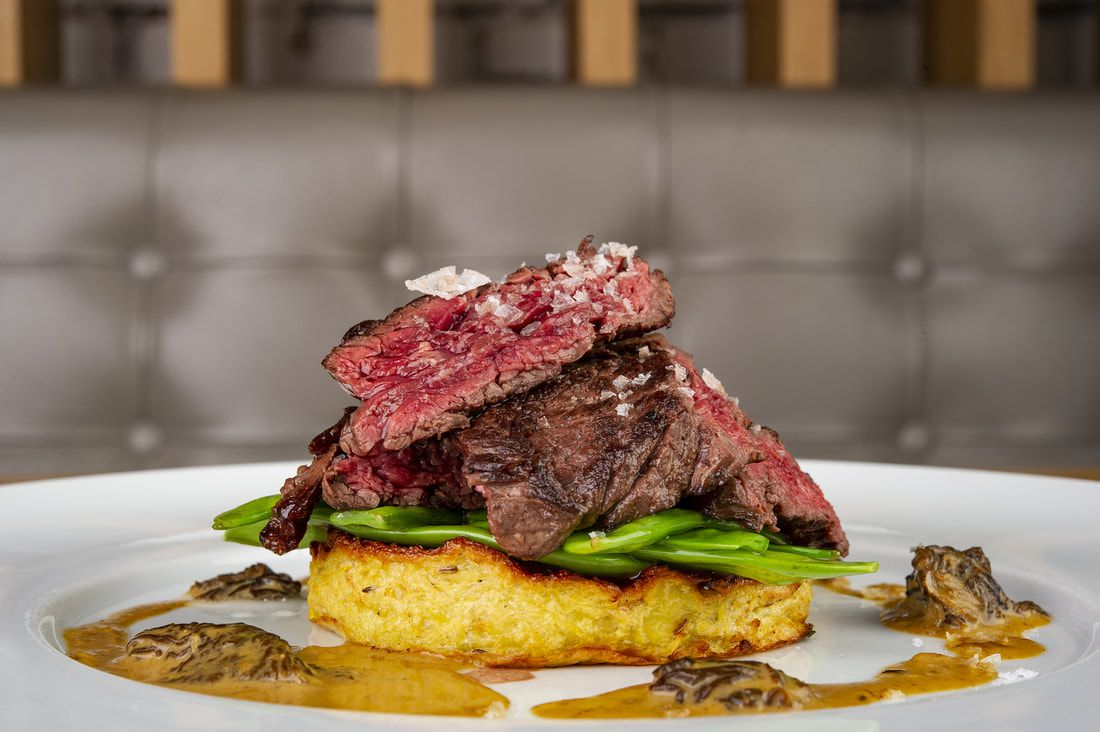 seared, rare steak sliced and piled on top of green vegetables and a potato based, fried item