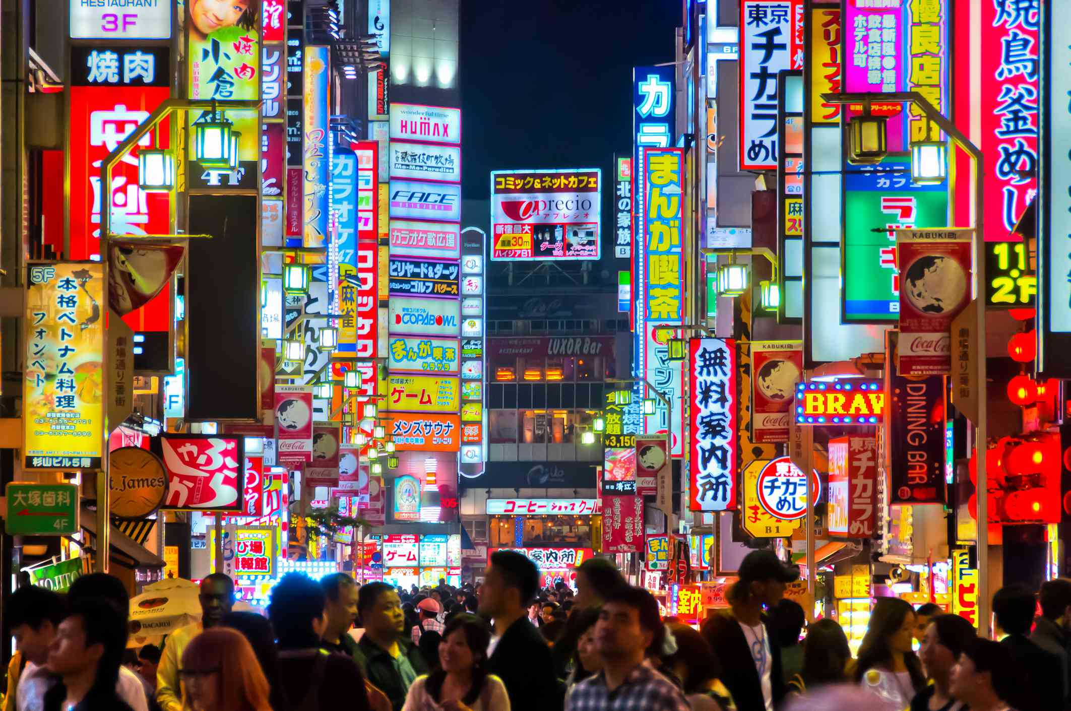 Colorful, illuminated signs in Shinjuku, Tokyo at night with many people walking in the street