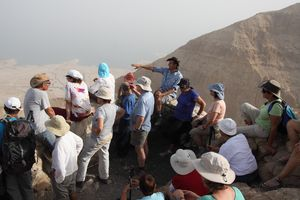 Hikers and guide in the desert looking at the Dead Sea