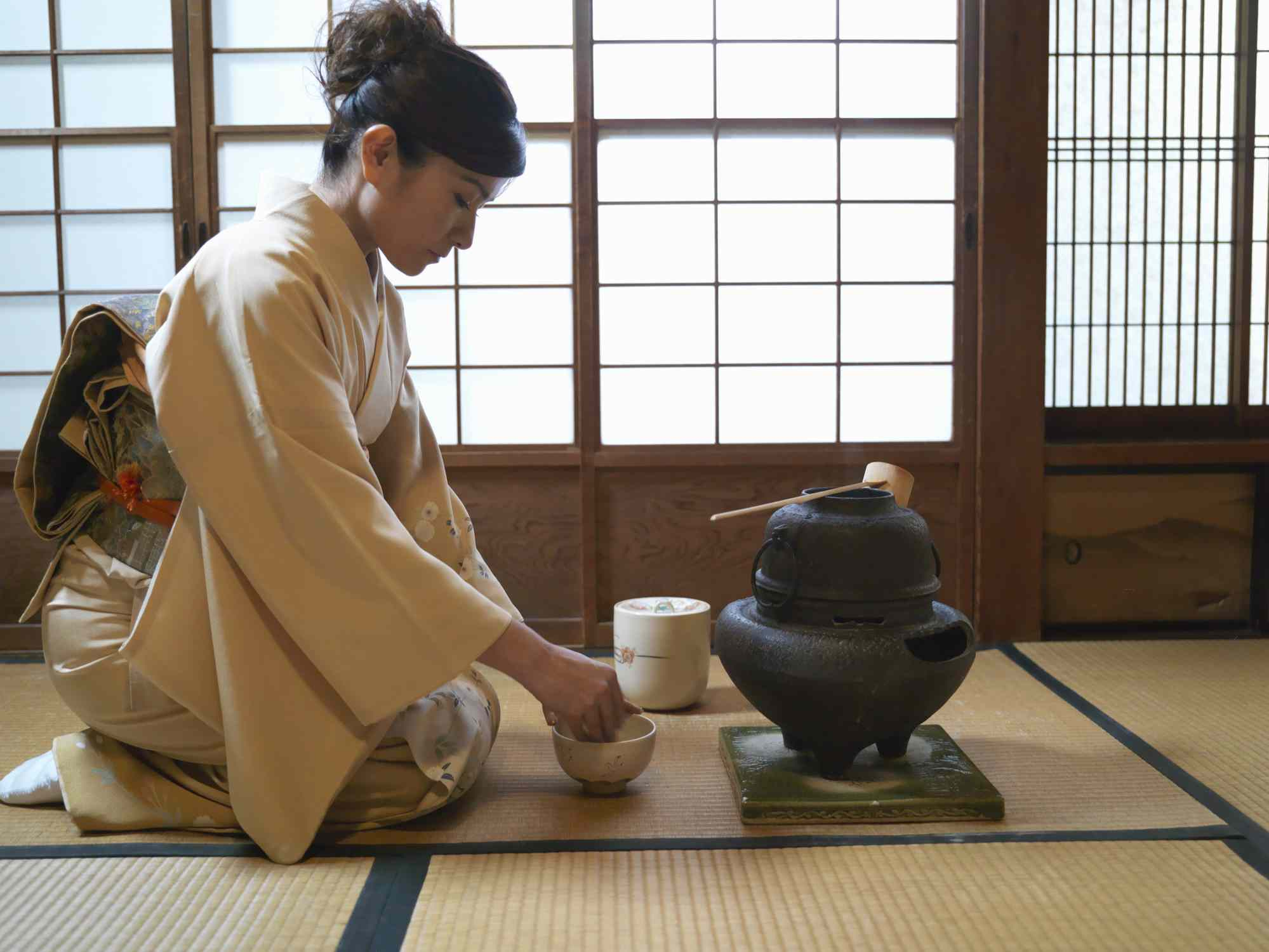 kneeling woman in a kimono doing a traditional japanese tea ceremony