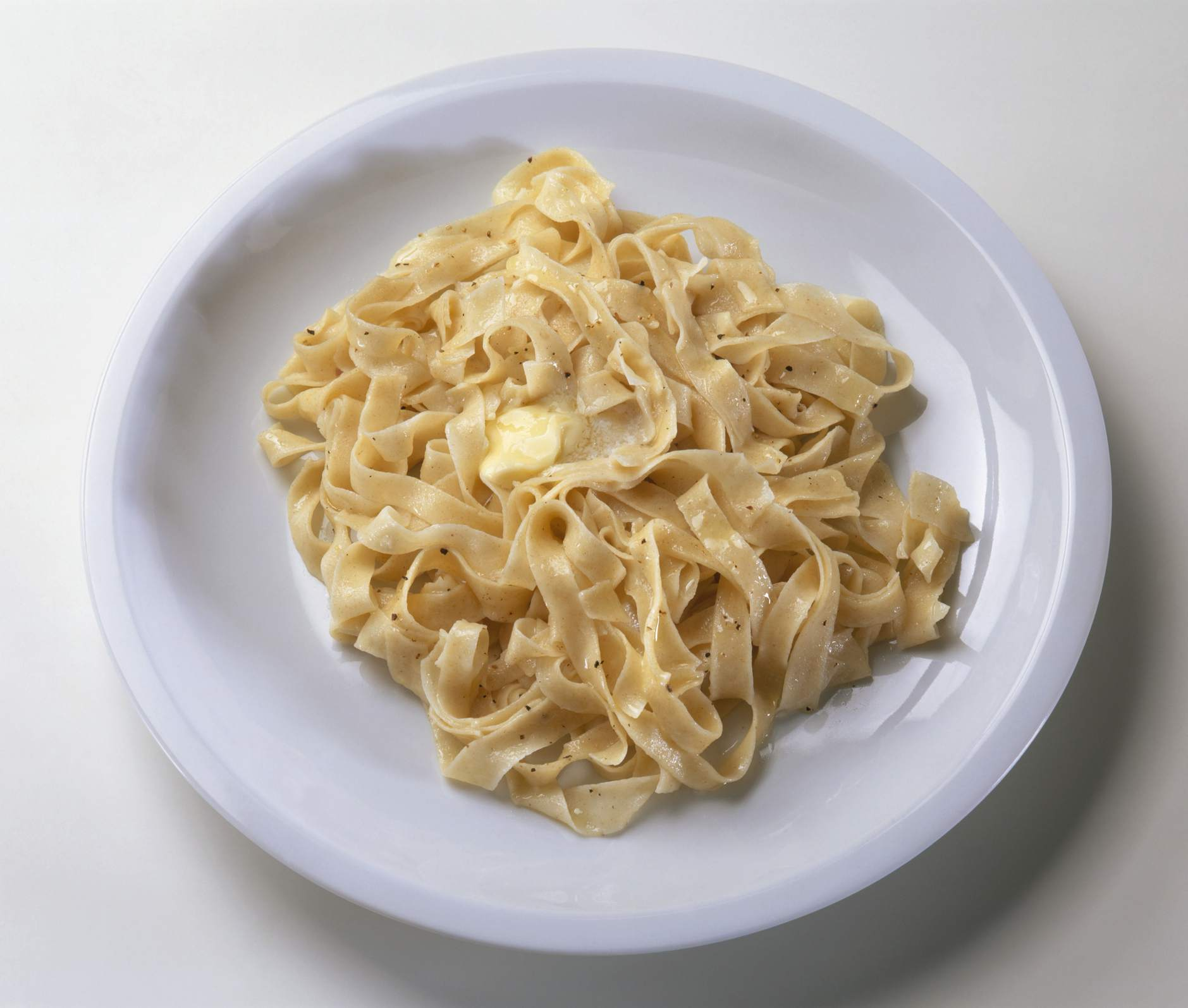 Fettucine served with butter and ground black peppercorn on white plate