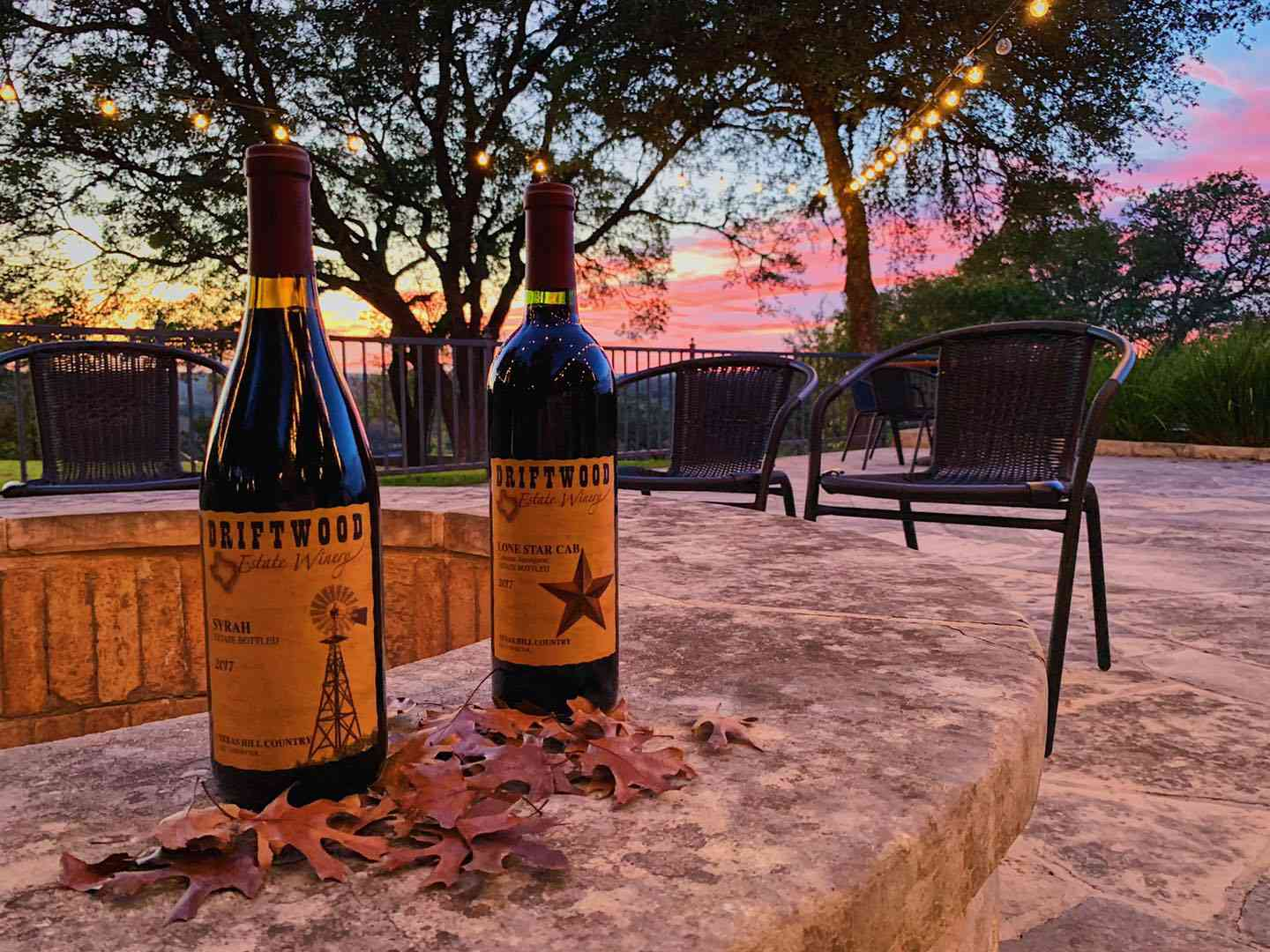 two bottles of wine on a fire pit at sunset