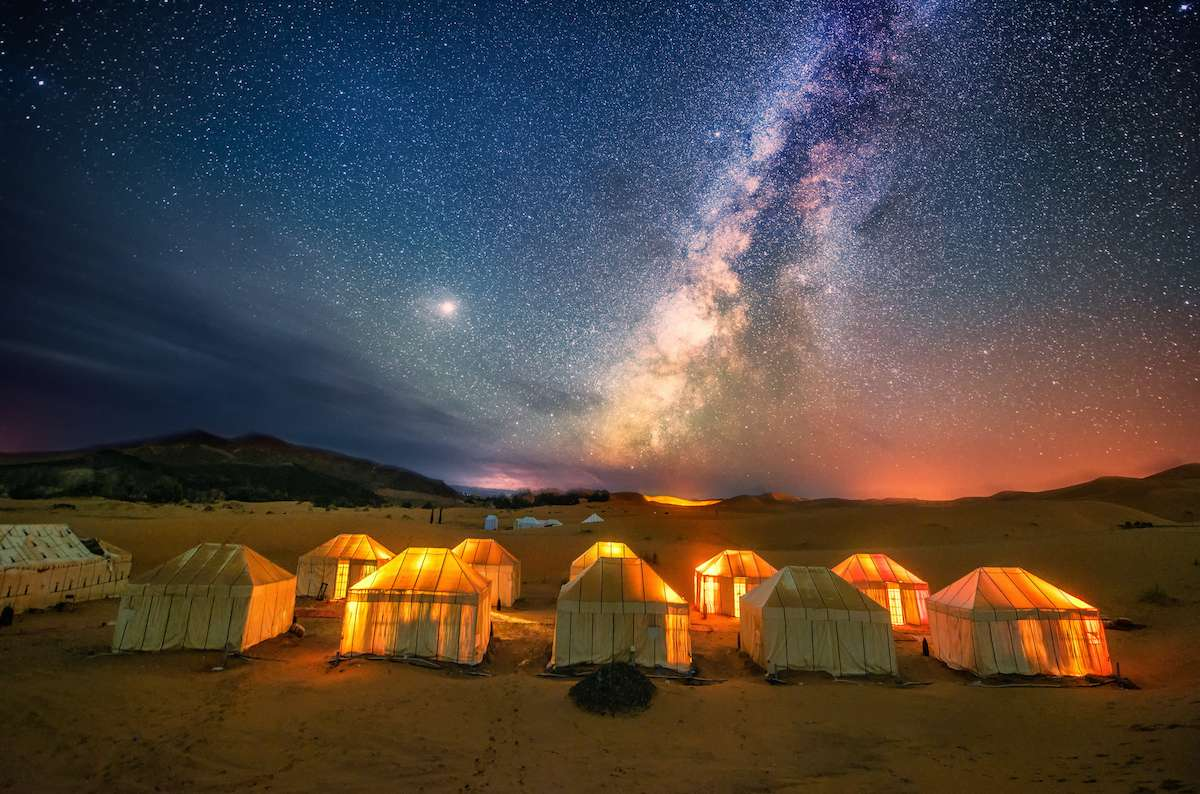 A star-filled sky hovers above a desert campsite