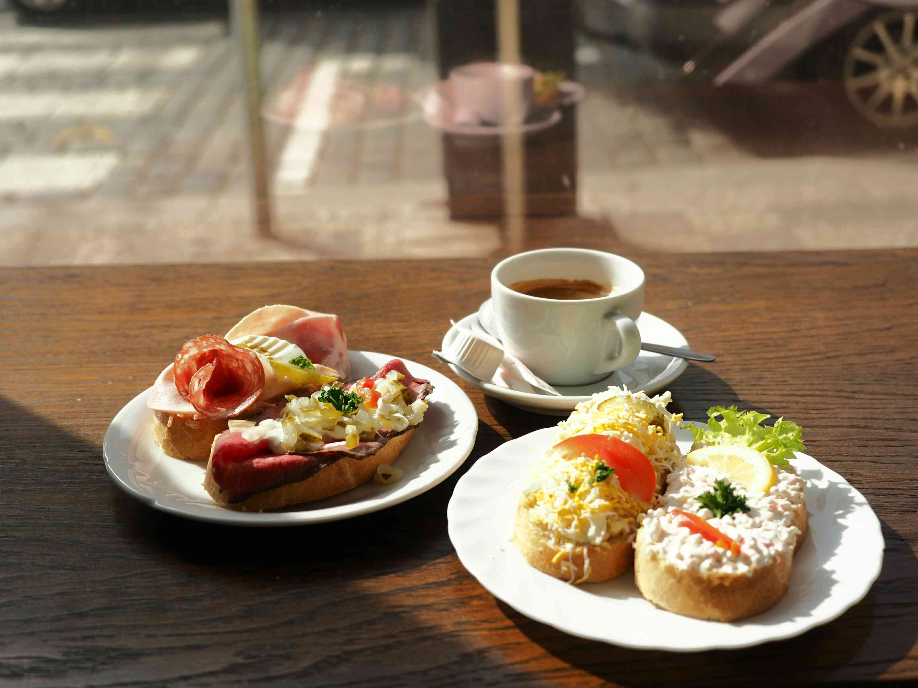 High Angle View Of four Open-face Sandwiches On two Plates With a cup of EspressoOn Table
