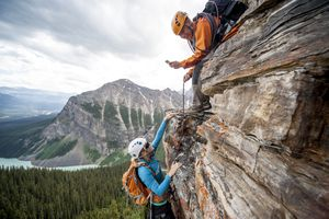 Climber takes picture of teammate ascending cliff