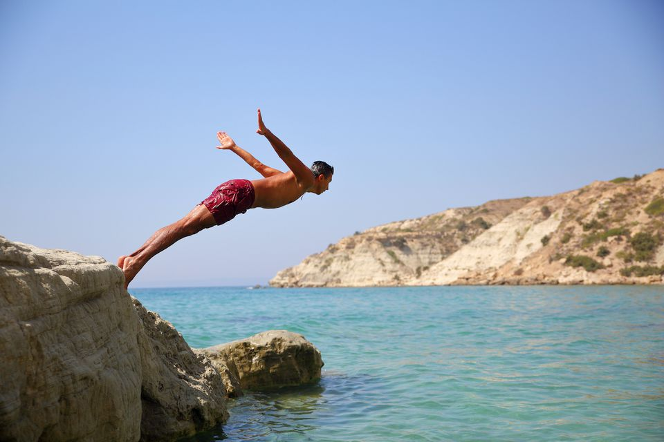 A man leaps off a high cliff into the ocean below