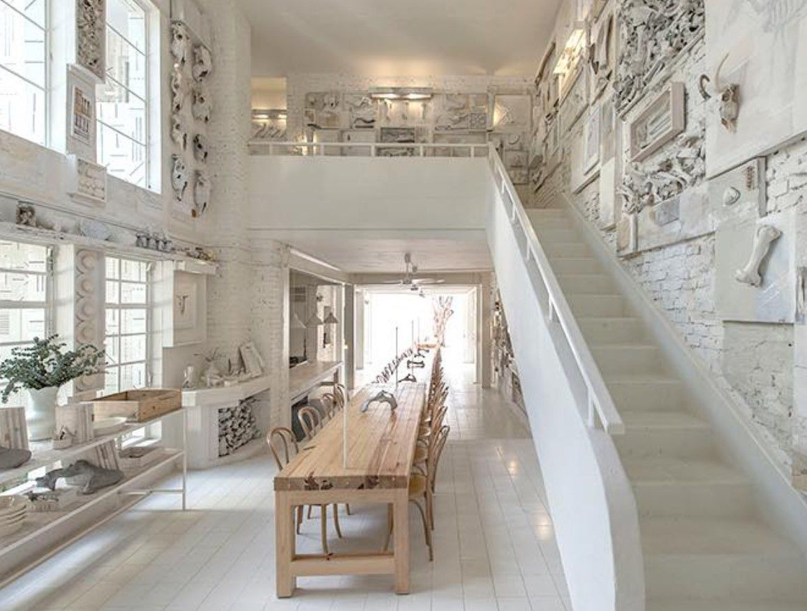 white restaurant with a loft area. ON the first levels theres is a very long light wood table. There is a set of stairs to the right leading upstairs to the lofted area