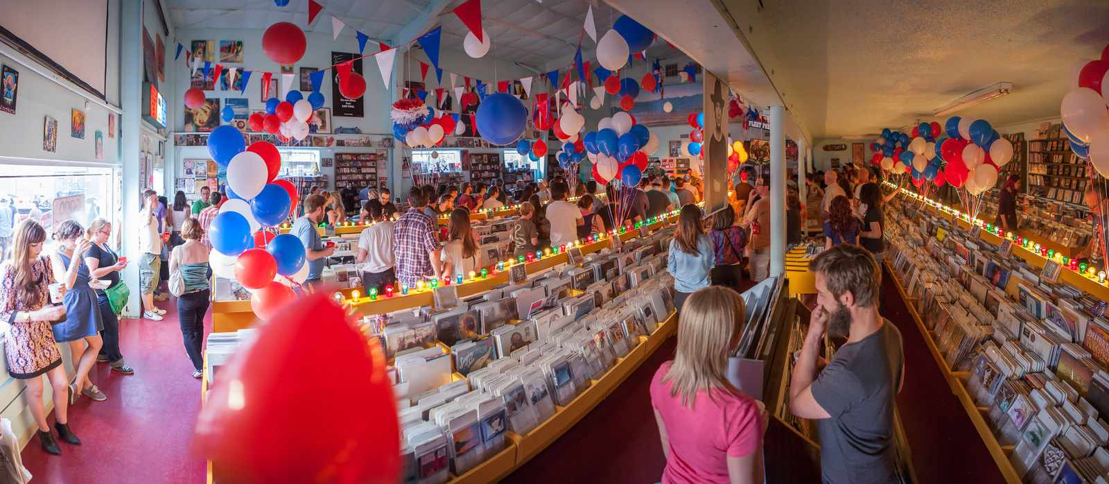 A record store filled with people, decorated with red, white and blue balloons and twinkling lights
