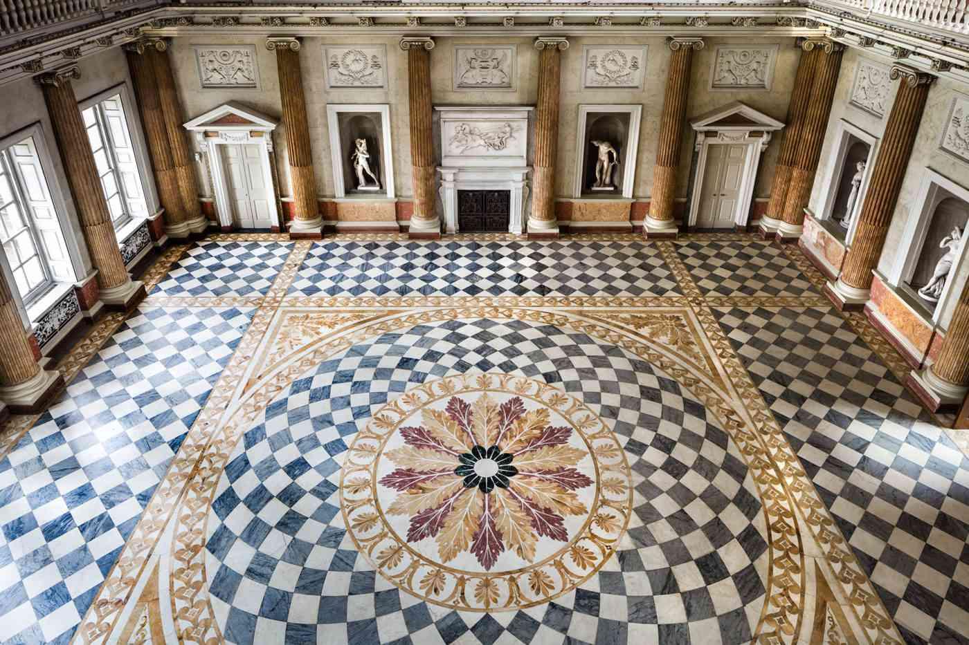 The Marble Saloon, a decorated marble-floored ballroom with roman columns along the wall, in Wentworth Woodhouse