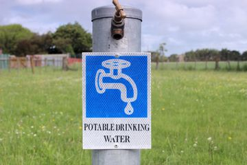 Potable drinking water sign and spigot at RV campsite.