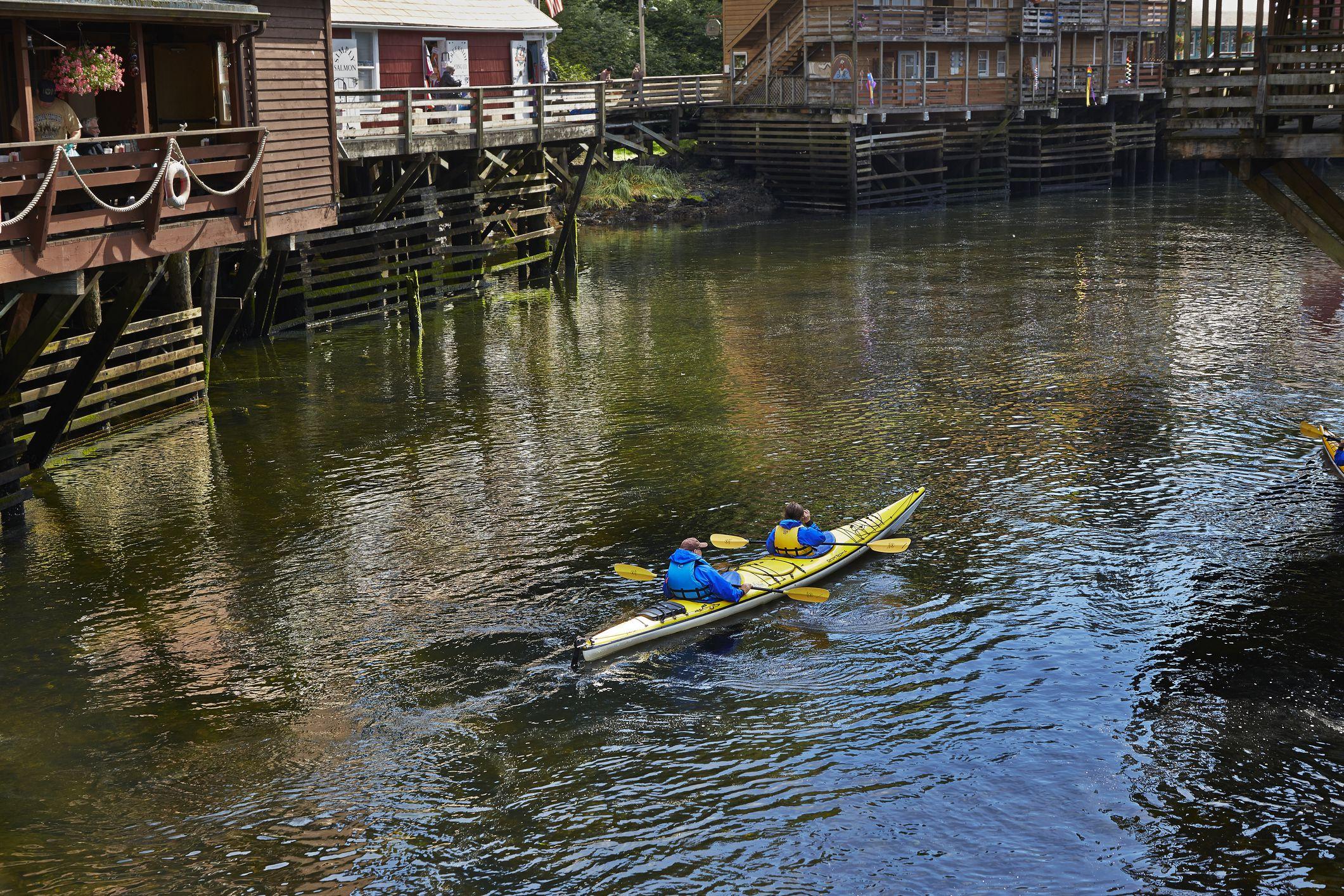 Two kayakers enjoy the sights of Ketchikan's historic Creek Street by paddling the Ketchikan Creek.