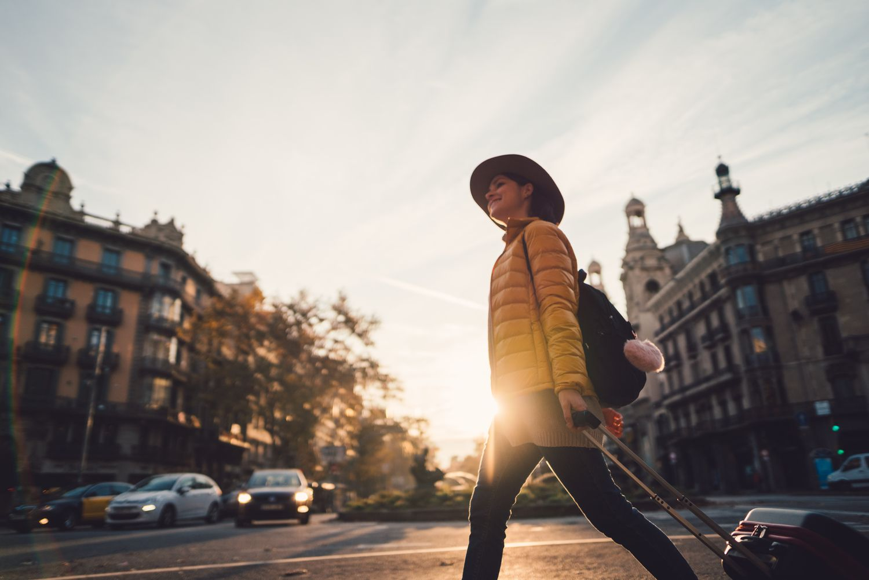 A tourist wheeling a suitcase through a street in Barcelona