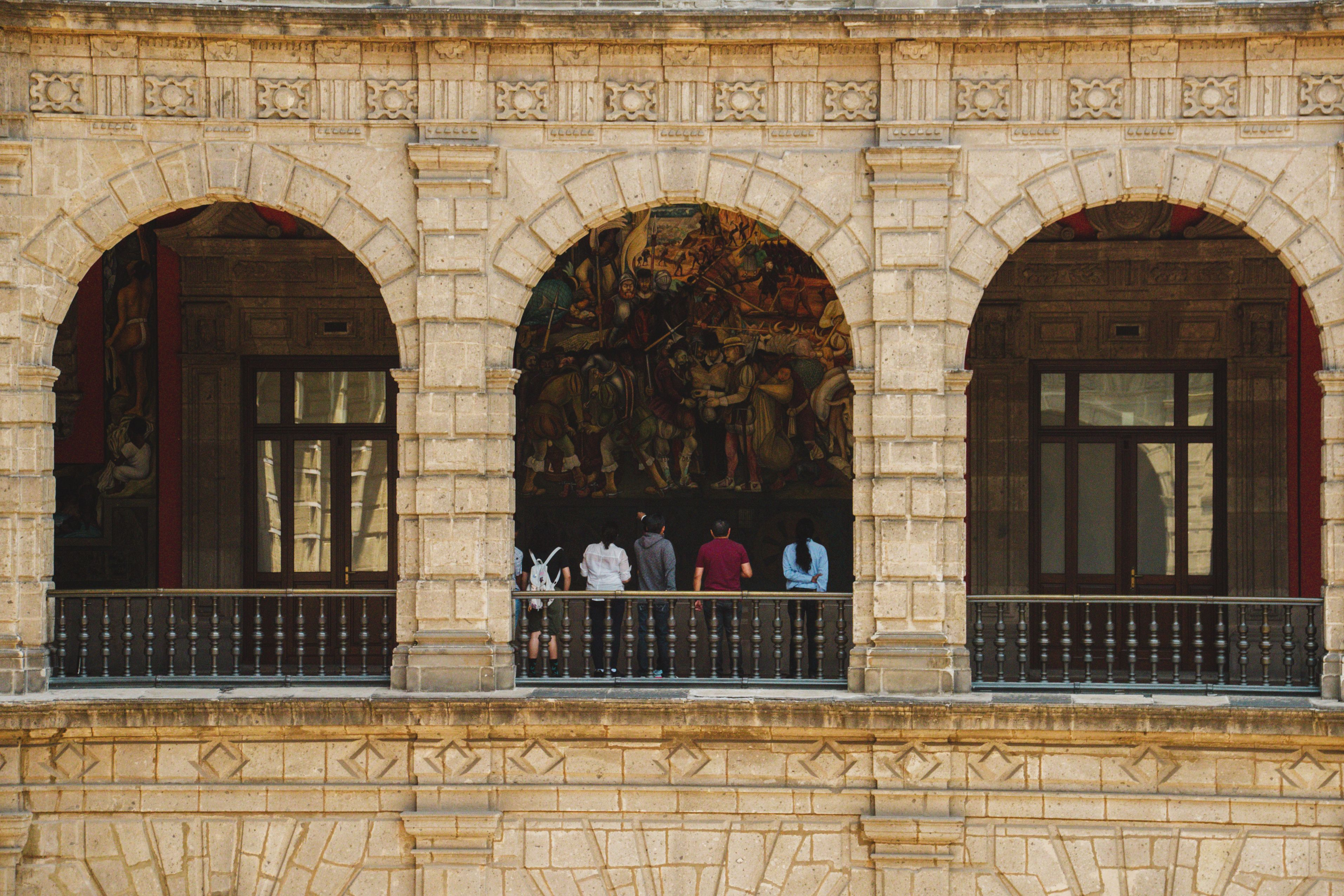 People looking at the mural inside the National Palace