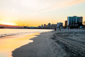 A beach in Long Beach california at sunset with buildings in the background