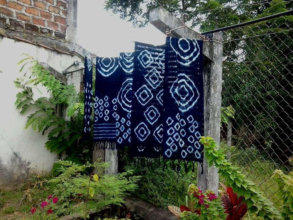 Five Indigo-dyed scarves hanging next to a fence in El Salvador