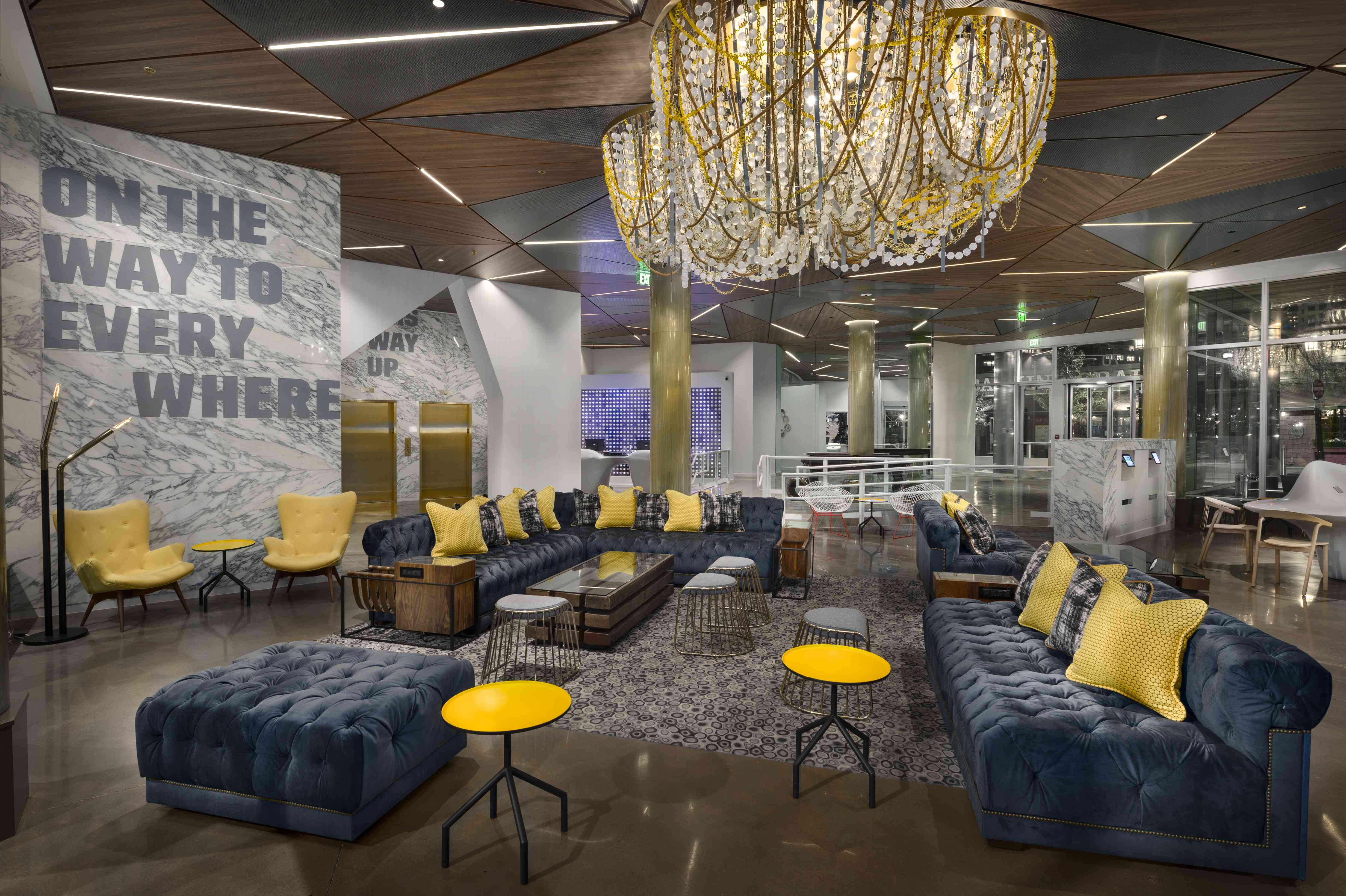hotel lobby with blue velvet couches, yellow and plaid accent pillows, and a modern chandelier over head