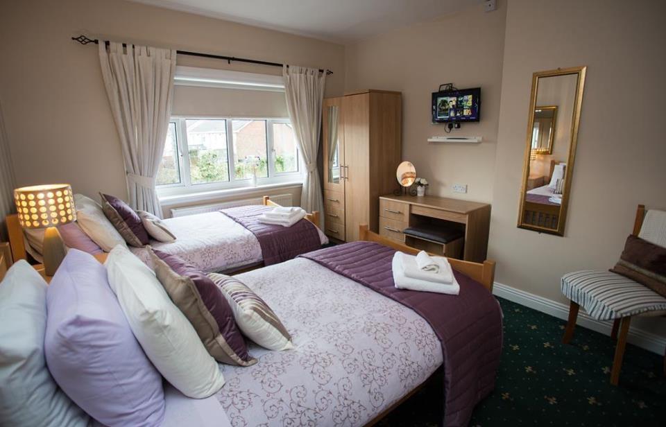 Dos camas individuales con sábanas de color púrpura