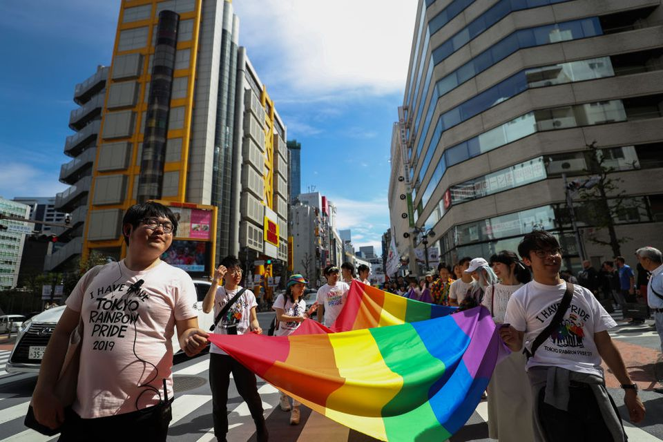 group of japanese people walking through a city's streets holding a very large rainbow pride flag