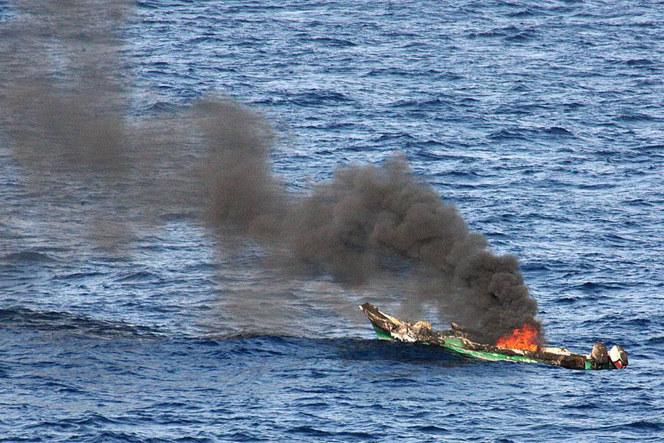 A suspected pirate skiff burns after being destroyed