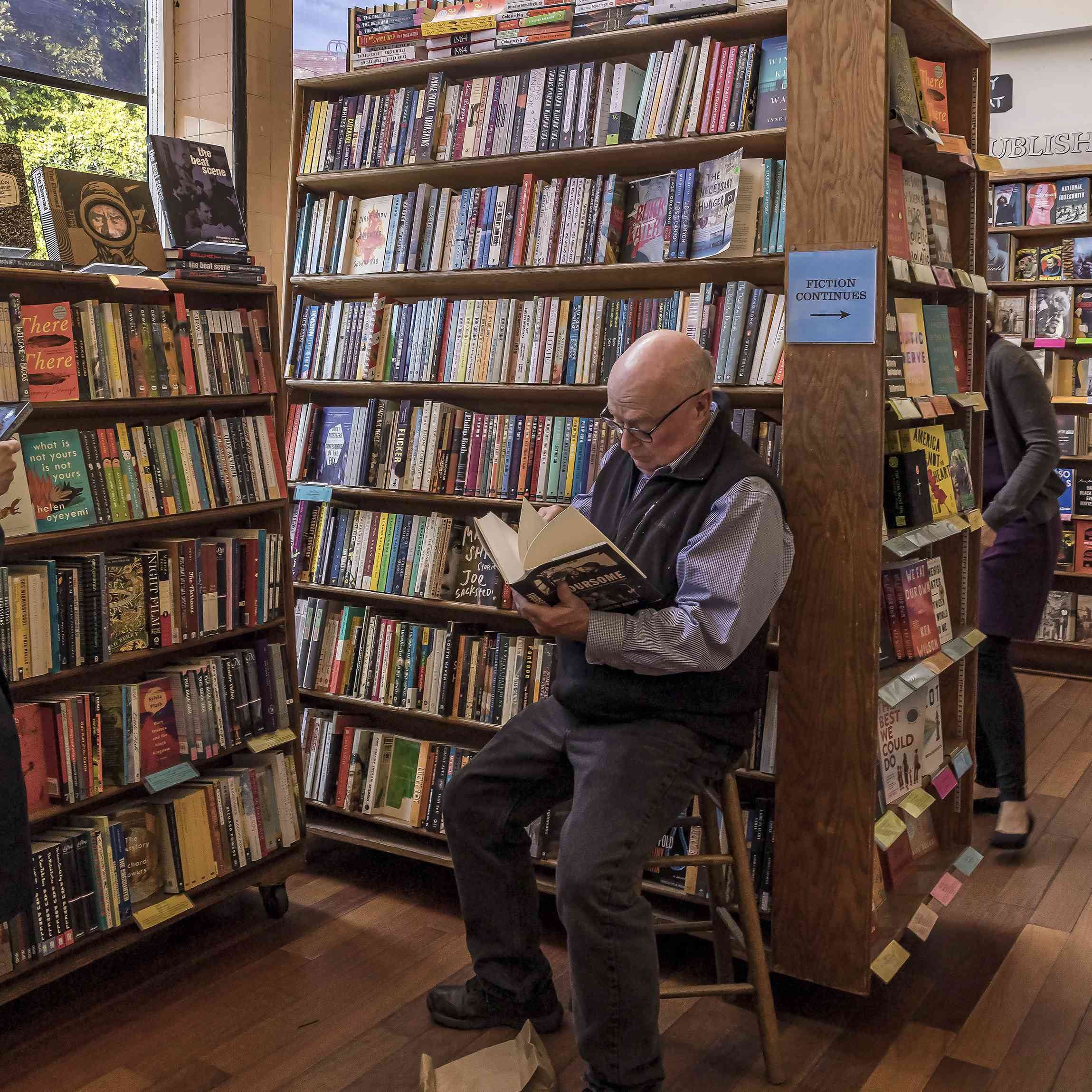 Un hombre que lee un libro dentro de City lights books