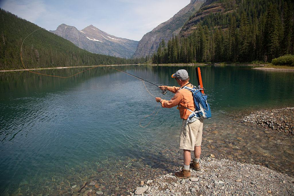 Man fly fishing on lake in Glacier National Park, Montana