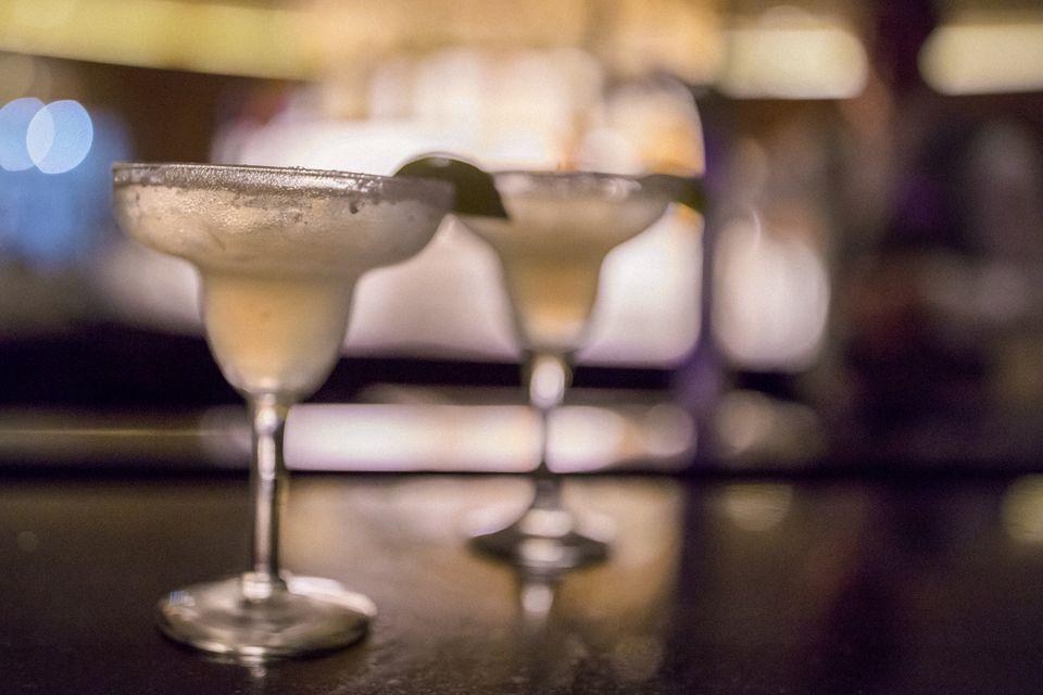 Dos margaritas perfectamente hechas sentadas en un bar.