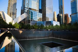 9-11 memorial waterfall with a view of the Oculus in the background