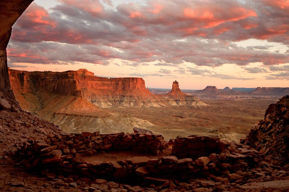 The red sandstone cliffs and towers of Canyonlands National Park stretch into distance.
