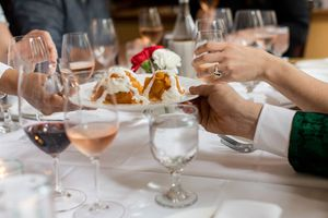 two arms passing off a plate over a table filled with wine glasses