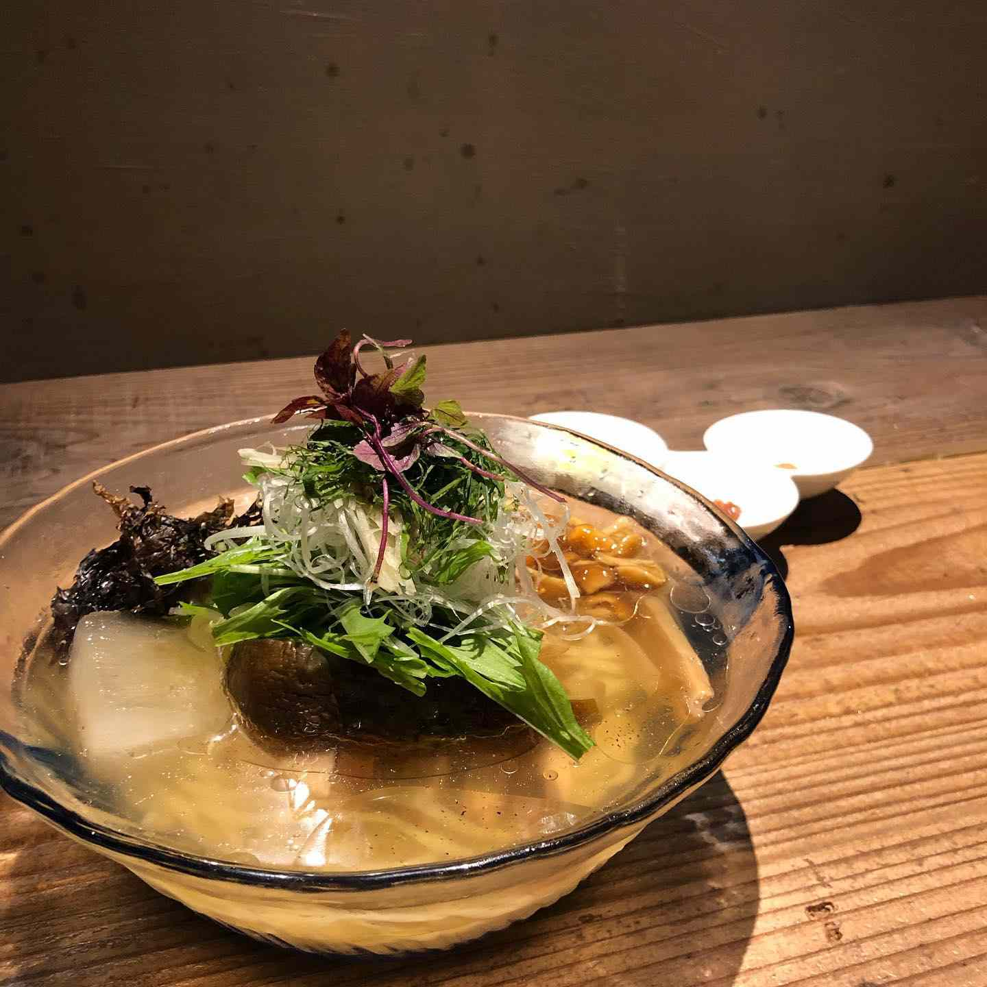 clear bowl of ramen topped with sprouts
