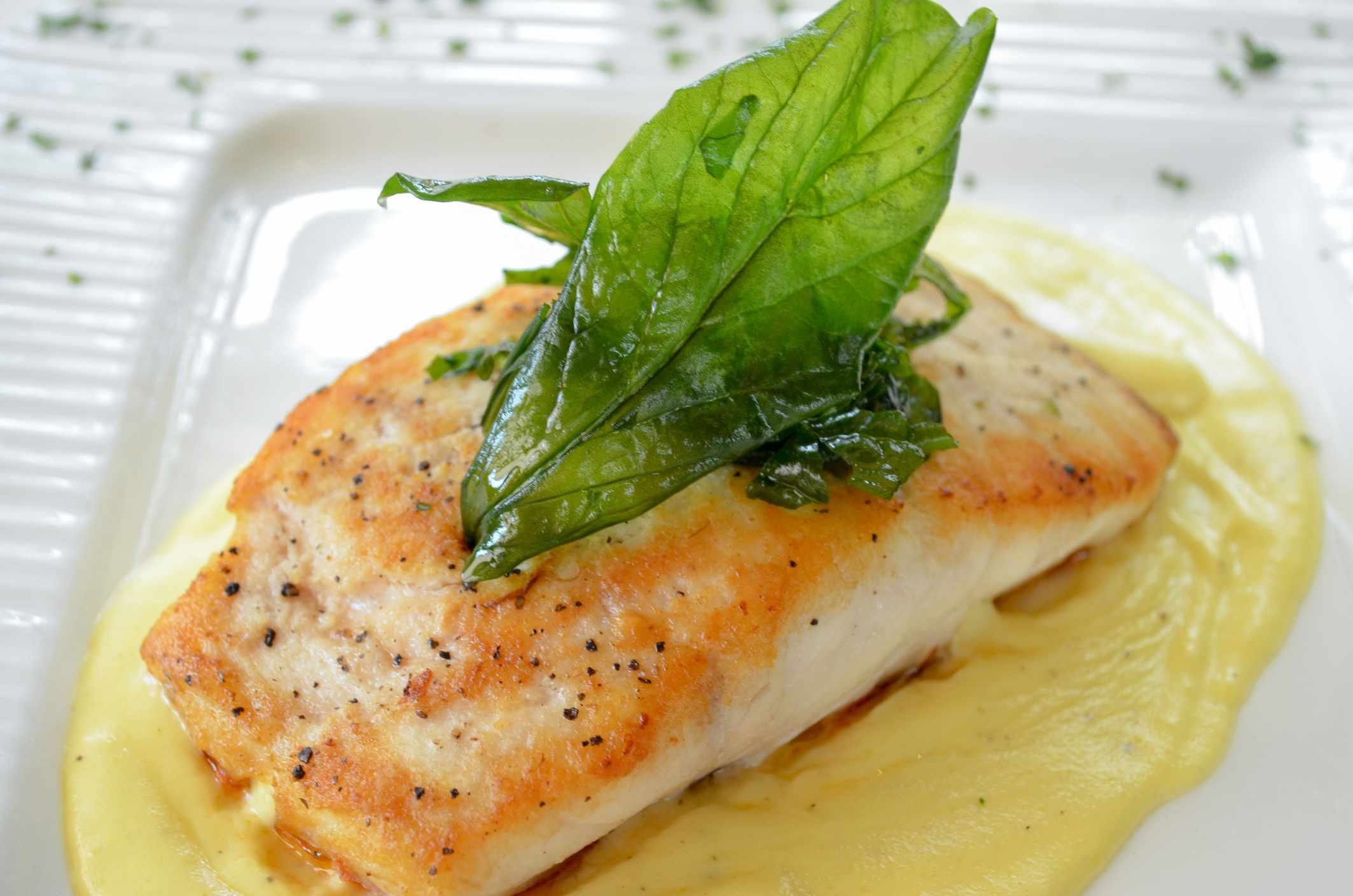 Red Snapper on a yellow sauce garnished with green leaves