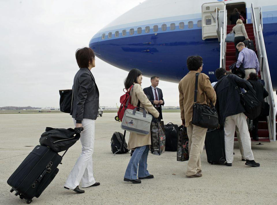 5fa9e365f0 Why One Bag Carry-On Travel  Airline passengers carry baggage into a plane.