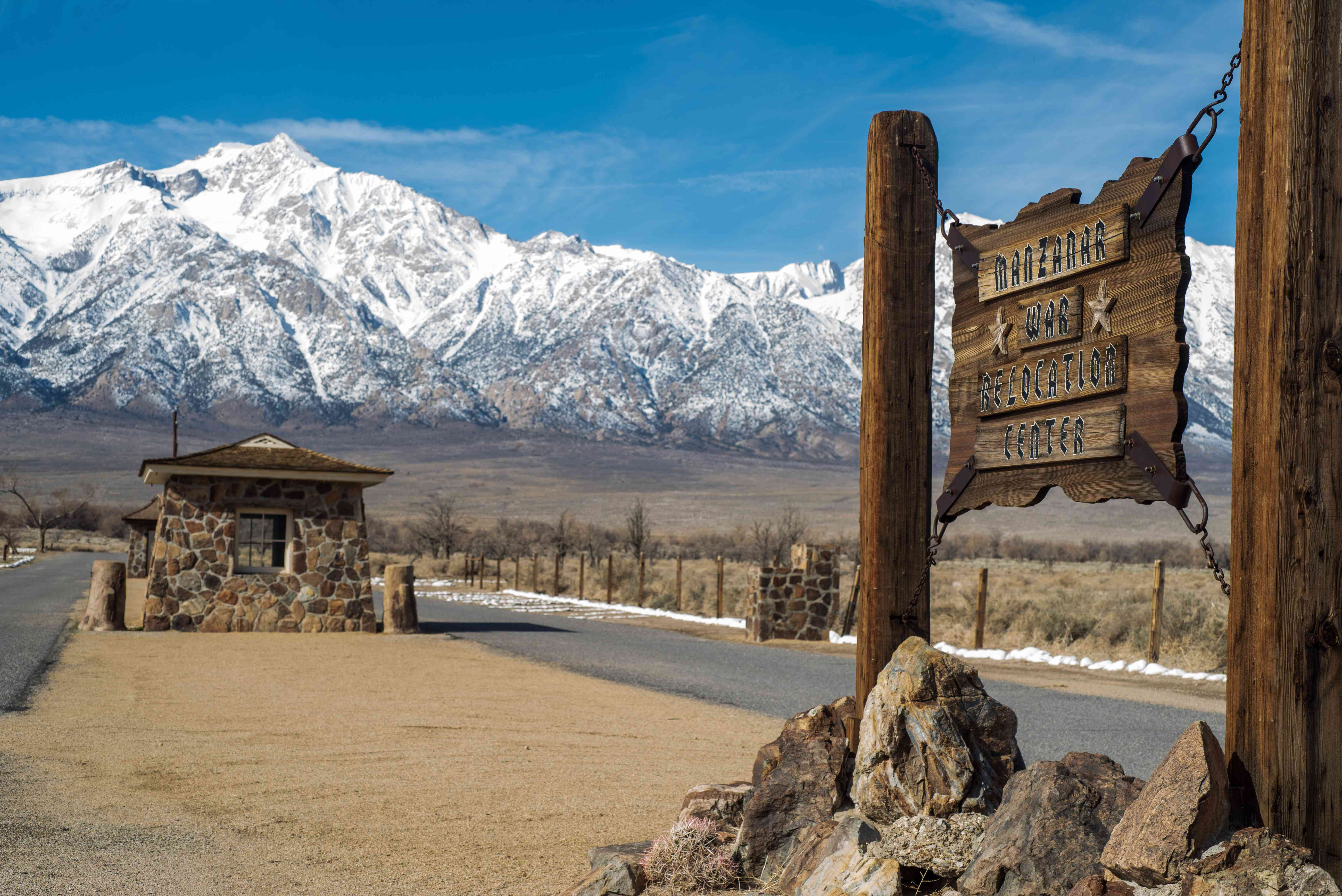 Manzanar Entrance Sign And Sentry Station With Snowcapped Mountains Against Sky