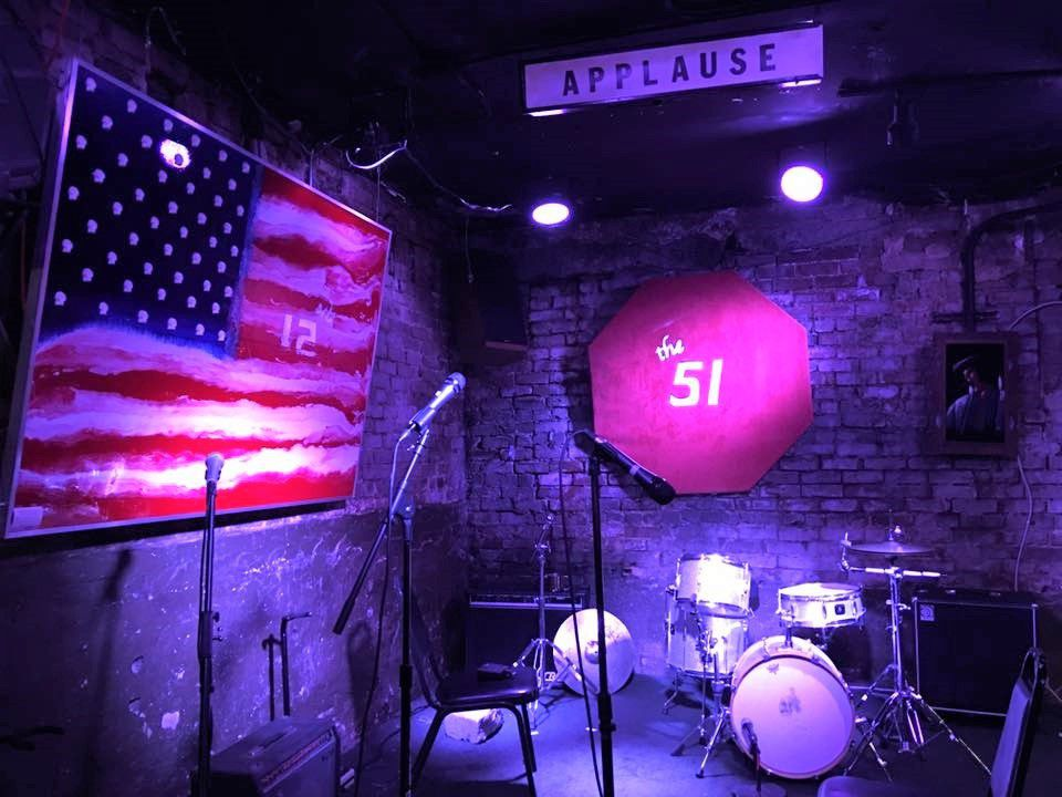 Drum set on a small corner stage with an american flag painting and a covered stop sign that reads