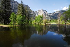 A lake with the waterfall in the background in Yosemite