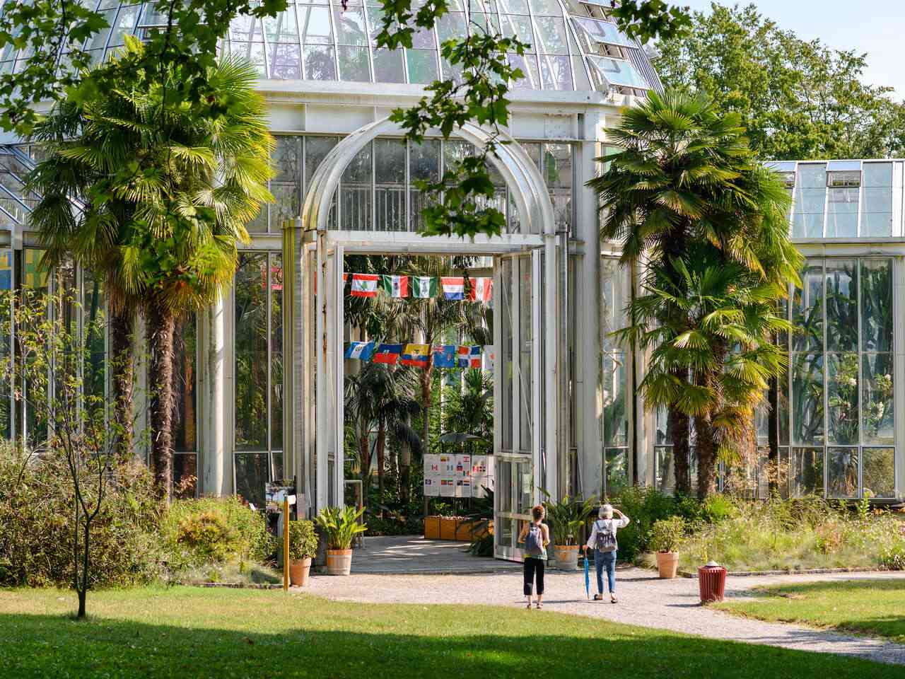 People standing in front of a large glass greenhouse with palm trees