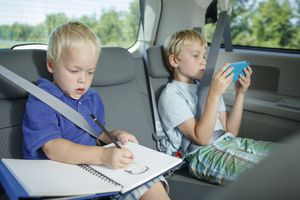 Boys drawing and playing video game in car