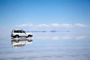4x4 vehicle crossing salt flats in Bolivia