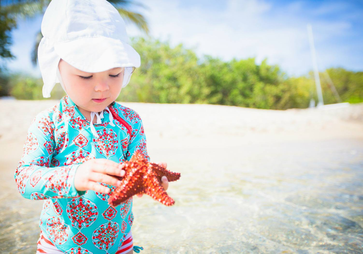Young girl holding star fish on St. Croix