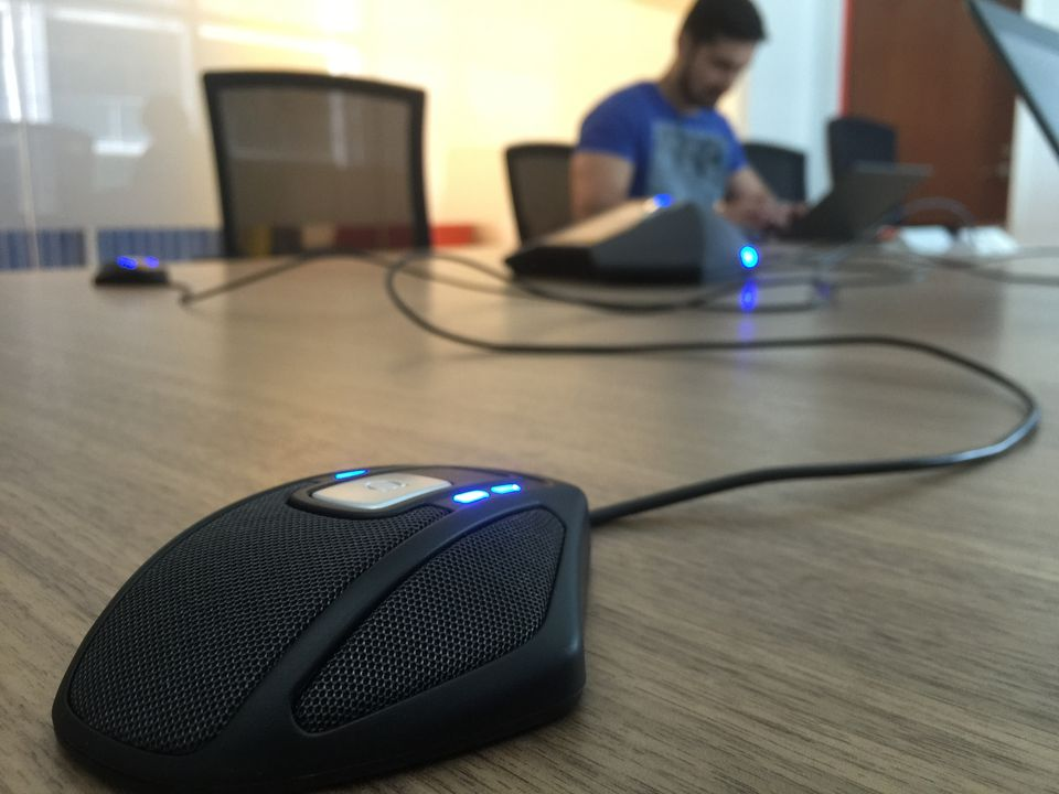 Close-Up Of Compute Mouse On Table With Man Working In Background At Office