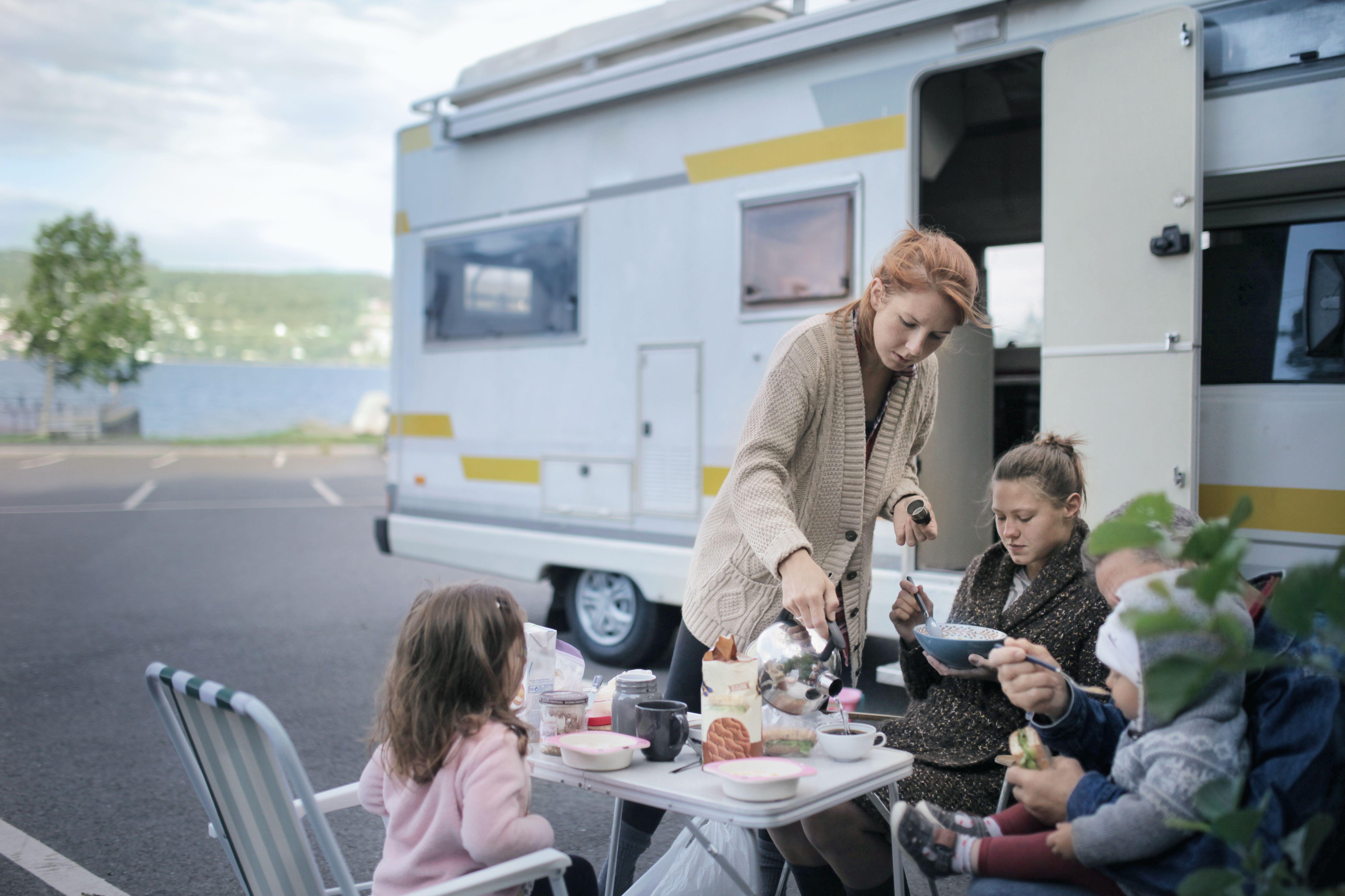 Family eating breakfast near campervan