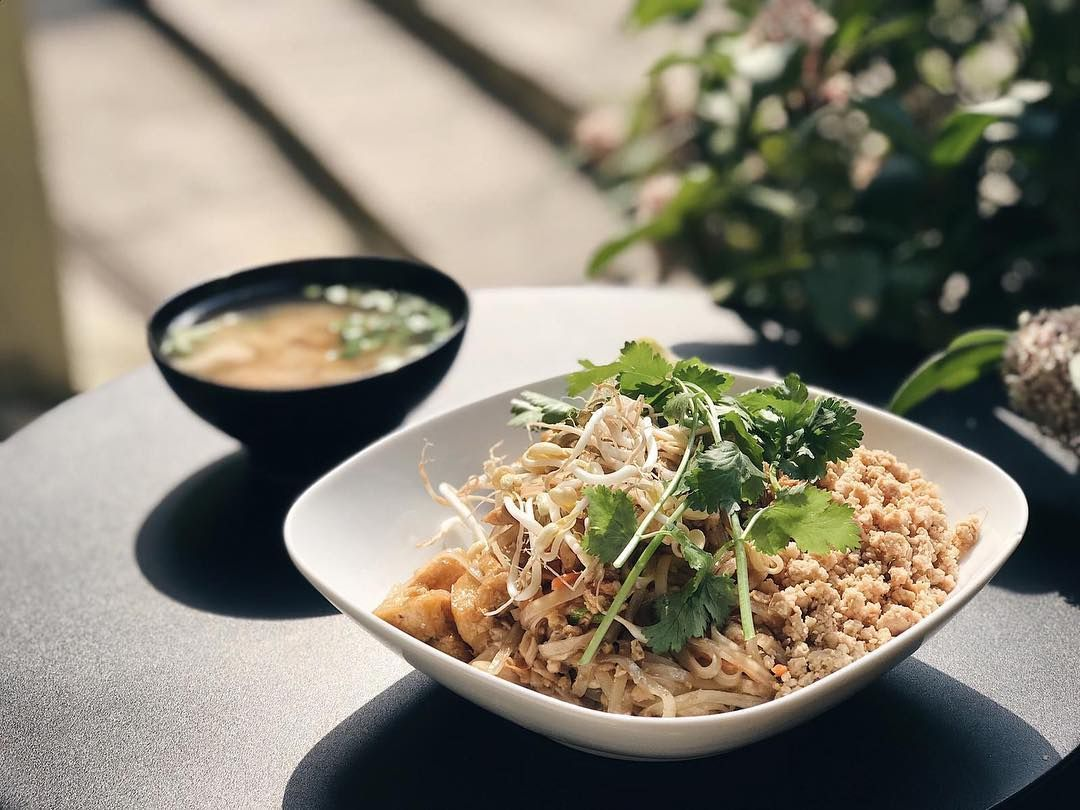 Pad thai in a sqaure bowl topped with cilantro. There is a black bowl of soup in the background