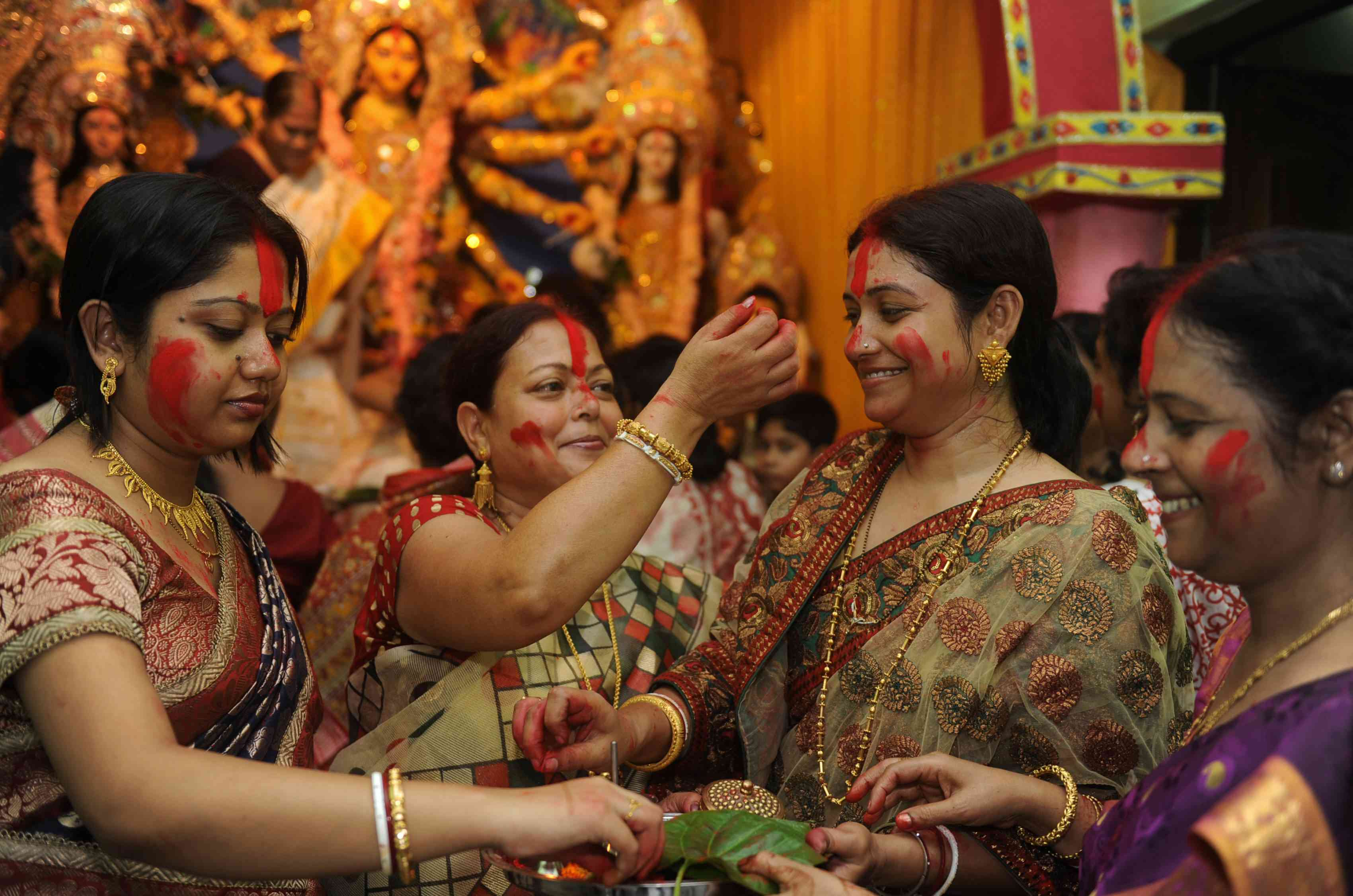 Las mujeres indias bengalíes aplican Sindoor (bermellón, una indicación de mujeres casadas) en las caras de los demás con motivo de Vijaya Dashami, Durga Puja.
