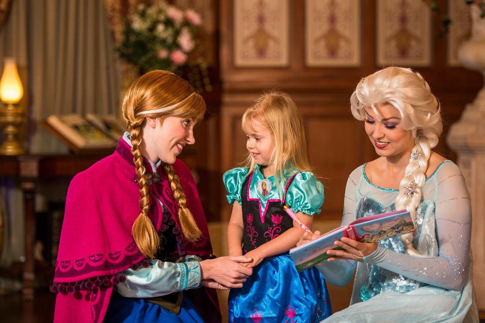 Anna y Elsa firman el libro de autógrafos de la niña