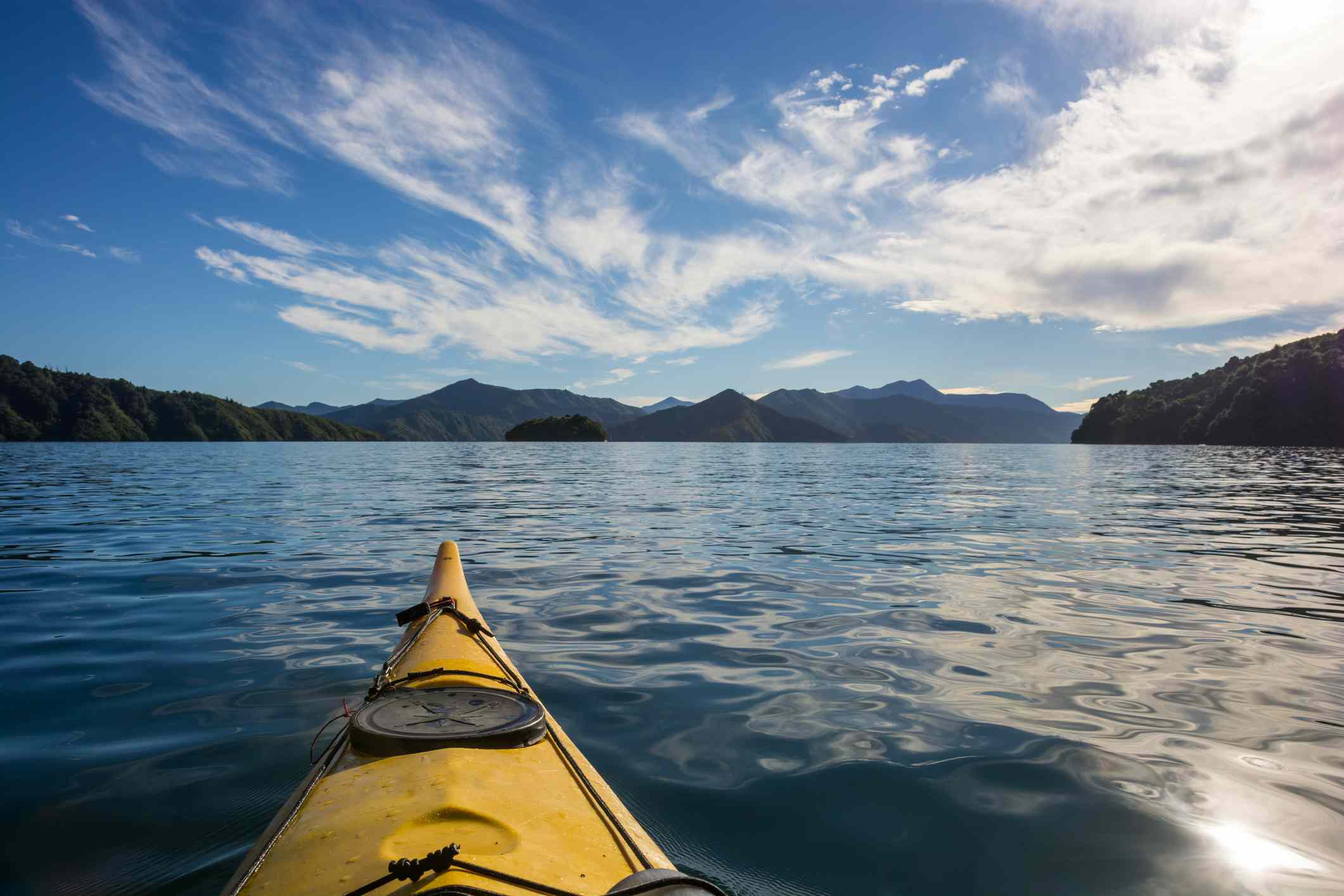 prow of a yellow kayak on the water with mountains in the distance and white clouds