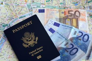 US passport and Euros on French map