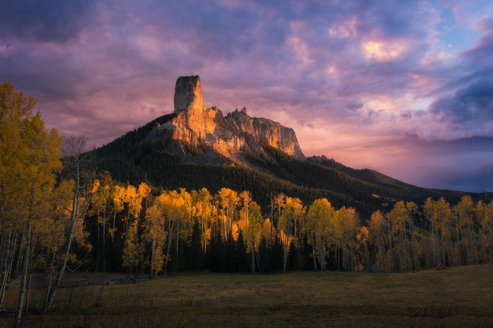 Last sunlight on Chimney Rock at Southwest colorado, surrounding by yellow aspen trees.