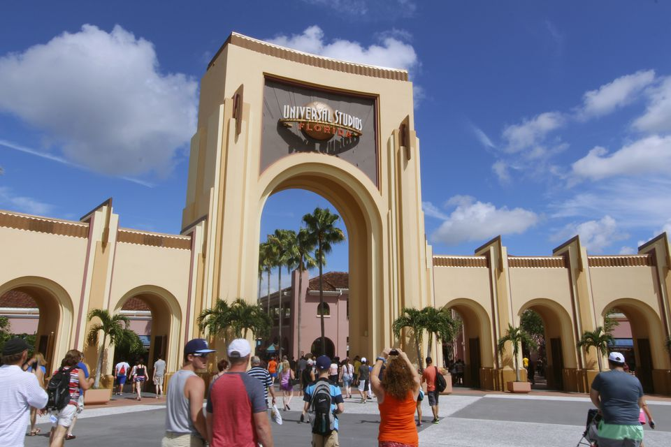 Entrance to Universal Orlando. People are walking and taking picture of the sign above the entrance arch